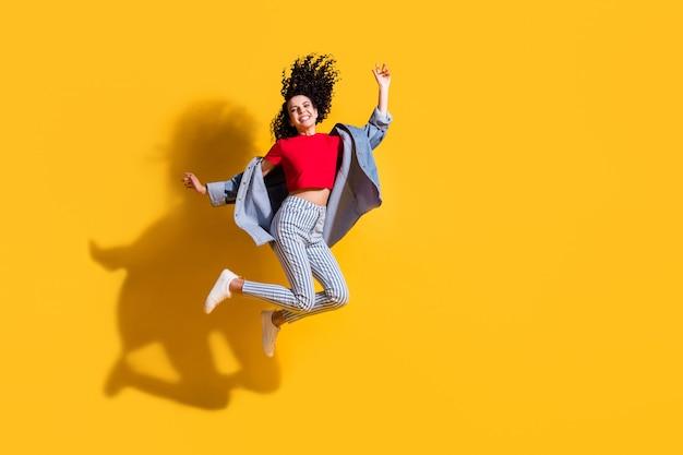 Pełna długość zdjęcie słodkie dziewczyny skok podnieś kolano ramię nosić paski dżinsy przycięte czerwone t-shirt kurtka trampki na białym tle żółty kolor tła