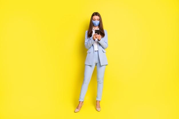 Pełna długość zdjęcie smm pracownik dziewczyna maska oddechowa użyj smartfona pisanie wiadomości covid post nosić niebieski marynarka kurtka spodnie spodnie wysokie obcasy na białym tle jasny połysk kolor tła
