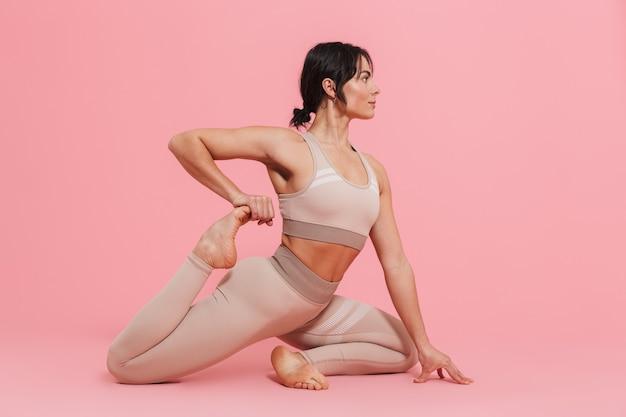 Pełna długość zdrowej, wysportowanej młodej kobiety ubranej w odzież sportową, wykonującą ćwiczenia rozciągające na białym tle nad różową ścianą