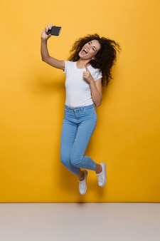 Pełna długość zdumionej kobiety w wieku 20 lat z kręconymi włosami, trzymającej smartfona i robiącej zdjęcie selfie izolowane na żółto