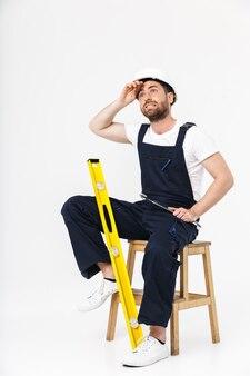 Pełna długość zmęczonego brodatego mężczyzny w kombinezonie i kasku siedzącym na krześle odizolowanym nad białą ścianą