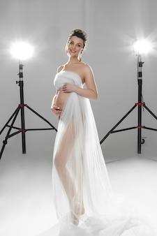 Pełna długość zmysłowej, wesołej, atrakcyjnej kobiety, która spodziewa się dziecka obejmującego brzuch podczas pozowania
