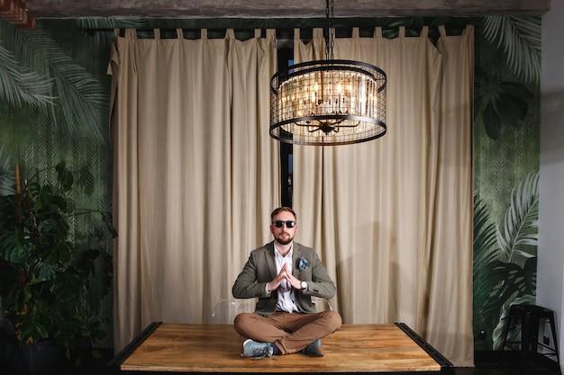Pełna długość zrelaksowanej dojrzałej młodej hipsterki siedzącej w okularach przeciwsłonecznych na stole w domu