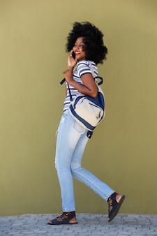 Pełna długości kobieta opowiada na telefonie komórkowym i odprowadzeniu z torbą