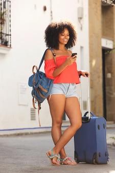 Pełna długości młoda kobieta z walizką i telefonem komórkowym