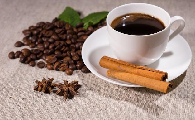 Pełna filiżanka kawy z cynamonem i przyprawami