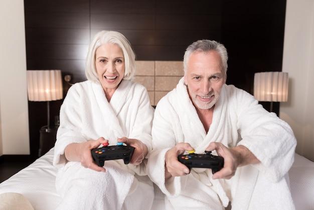Pełna frajdy. zachwycona, uśmiechnięta para w podeszłym wieku trzymająca konsole do gier, leżąca na łóżku i wyrażająca szczęście