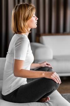 Pełna kobieta siedzi na kanapie