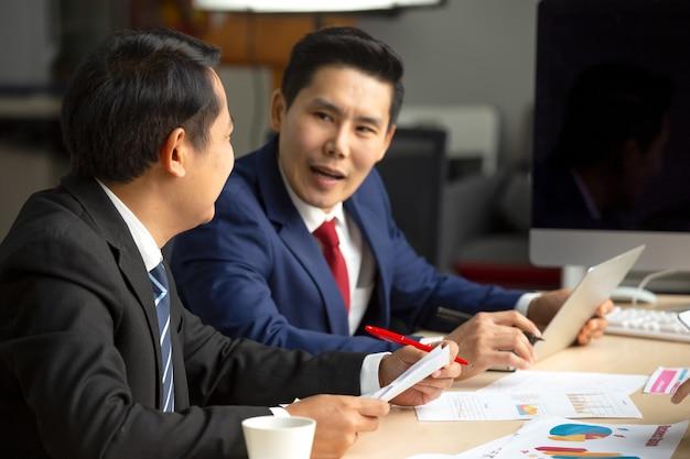 Pełna koncentracja w pracy. grupa młodzi ludzie biznesu pracuje i komunikuje podczas gdy siedzący przy biurowym biurkiem wraz z kolegami siedzi w tle