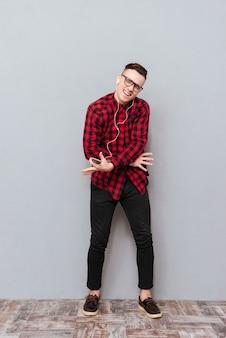 Pełna langth szczęśliwy młody hipster w okularach, słuchanie muzyki w słuchawkach i taniec w studio z zamkniętymi oczami. na białym tle szarym tle