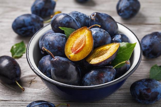 Pełna miska dojrzałych owoców śliwki na drewnianym stole