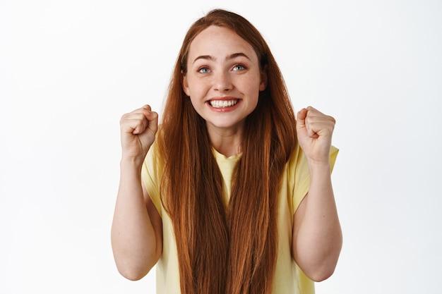 Pełna nadziei dziewczyna patrząc na ekran z zaciśniętymi pięściami i podekscytowaną uśmiechniętą twarzą stawia zakład na biały.
