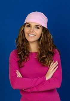 Pełna nadziei kobieta ubrana w różowy szalik na białym tle na białej ścianie