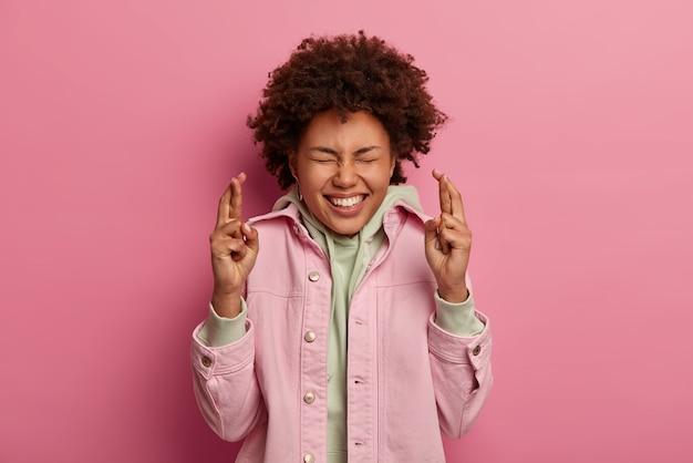 Pełna nadziei optymistyczna kręcona kobieta krzyżuje oba palce, przewiduje dobre wieści, wierzy, że marzenia się spełniają, nosi bluzę z kapturem i różową kurtkę, uśmiecha się szeroko