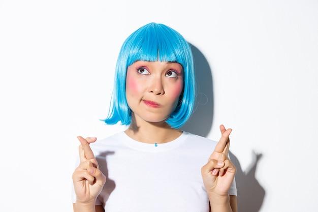 Pełna nadziei piękna azjatka w niebieskiej peruce wypowiadająca życzenie, rozmarzona w lewym górnym rogu i skrzyżowanymi palcami