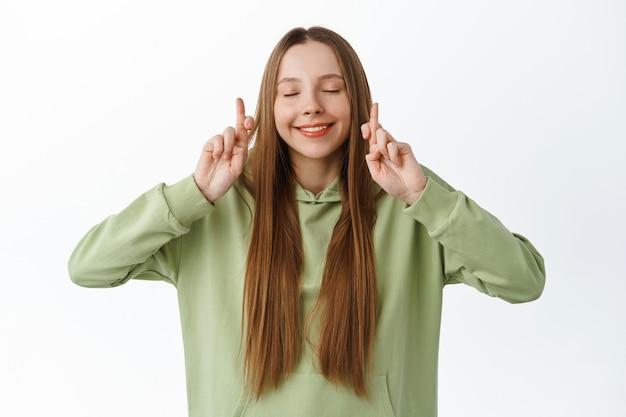 Pełna nadziei studentka krzyżuje palce i zamyka oczy, błagając o szczęście na egzaminie, oczekując dobrych wieści, stojąc optymistycznie na białej ścianie