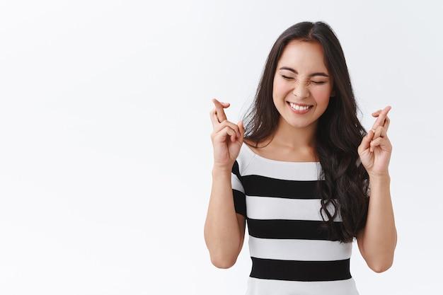 Pełna nadziei szczęśliwa urocza kobieta z azji wschodniej w pasiastym t-shircie trzyma skrzyżowane palce, wierzy, że marzenia się spełniają, życząc z zamkniętymi oczami i optymistycznym uśmiechem, oczekując ważnych wiadomości, białe tło