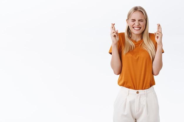 Pełna nadziei urocza, optymistyczna młoda blond dziewczyna w stylowej koszulce, spodniach, ze skrzyżowanymi palcami i uśmiechnięta z zamkniętymi oczami, życząca, czekająca na spełnienie marzeń, chęć osiągnięcia osiągnięć, białe tło