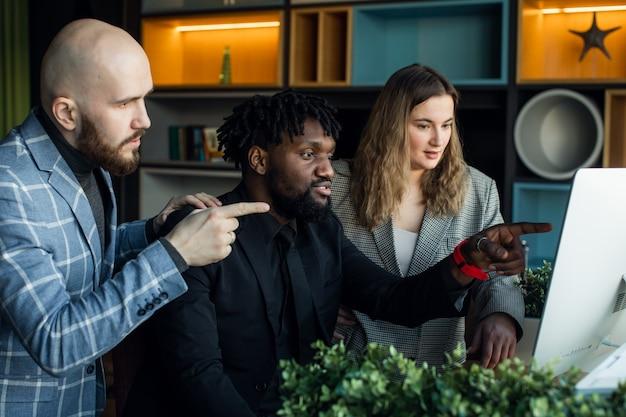 Pełna ocena w pracy. grupa młodych biznesmenów pracujących i komunikujących się siedzi w biurze wraz z kolegami. wysokiej jakości zdjęcie