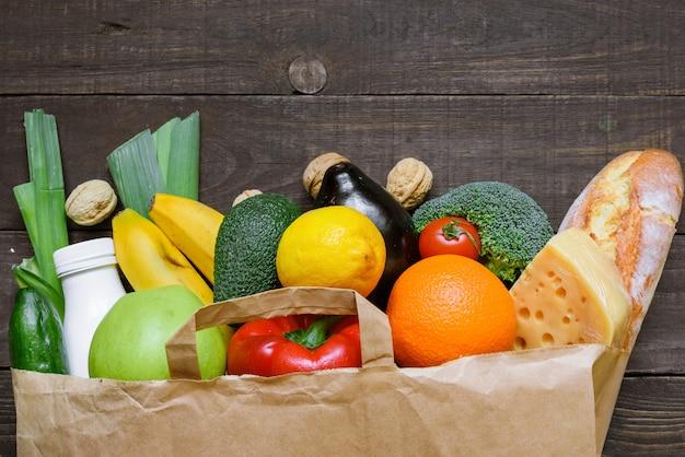 Pełna papierowa torba na różne zdrowe jedzenie na prosty drewniany stół. jedzenie wegetariańskie