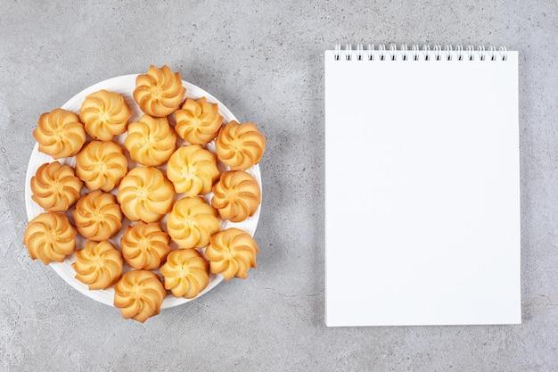 Pełna porcja domowych ciasteczek obok notatnika na marmurowym tle. wysokiej jakości zdjęcie