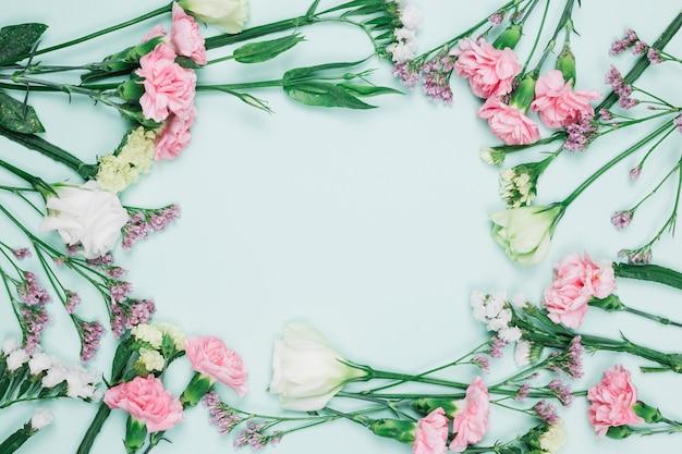 Pełna rama świeżych kwiatów ozdobnych z miejsca w centrum na niebieskim tle