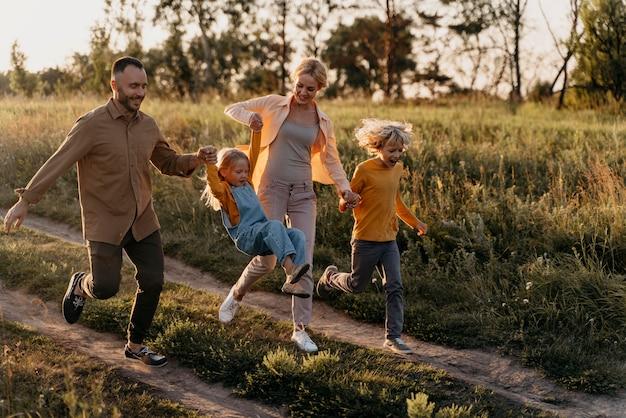 Pełna rodzina biegająca na łące