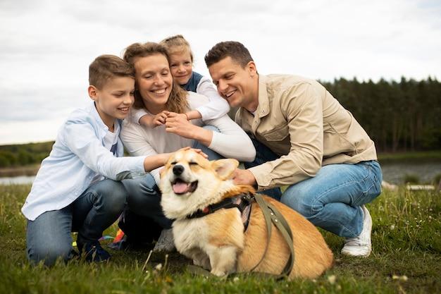 Pełna rodzina strzał z uroczym psem na zewnątrz