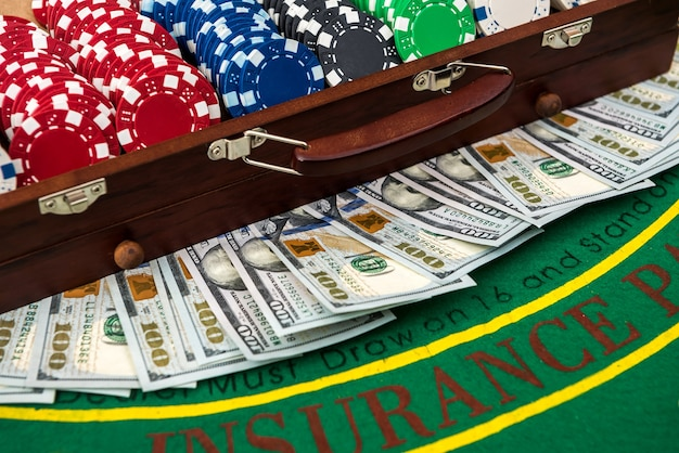 Pełna skrzynka żetonów pokerowych z dolarami na stole do gry. poker.