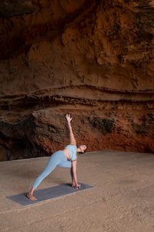 Pełna sprawna kobieta robi joga na zewnątrz