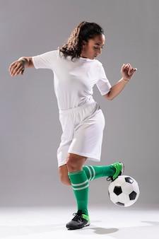 Pełna strzał dysponowana kobieta bawić się z piłką