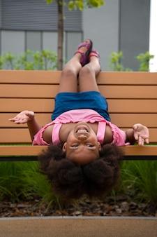 Pełna strzał dziewczyna leżąca na ławce