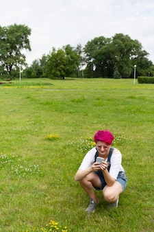 Pełna strzał dziewczyna na trawie z telefonem