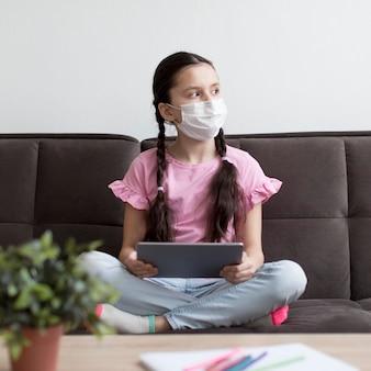 Pełna strzał dziewczyna nosi maskę medyczną