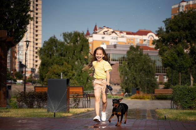 Pełna strzał dziewczyna wyprowadzająca psa