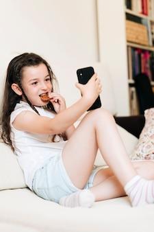Pełna strzał dziewczyna z ciastkiem bierze selfie