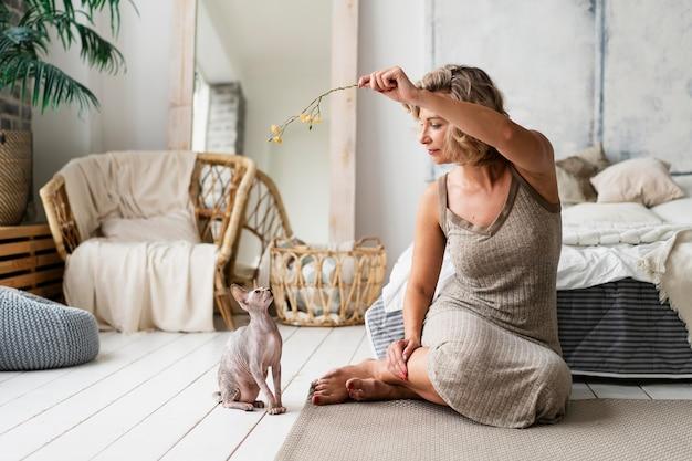 Pełna strzał kobieta bawiąca się z bezwłosym kotem