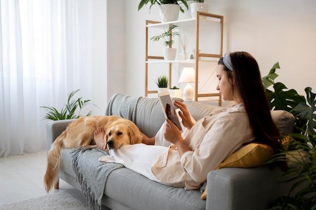 Pełna strzał kobieta i słodki pies na kanapie