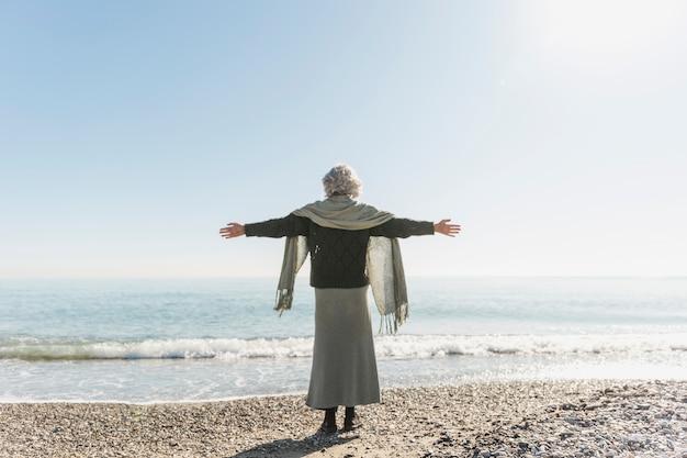 Pełna strzał kobieta medytuje nad morzem