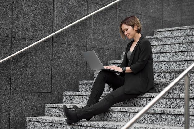 Pełna strzał kobieta na schodach z laptopem