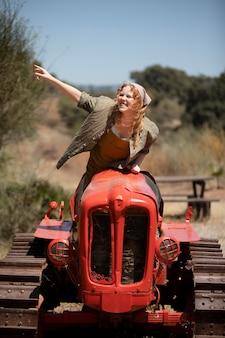 Pełna strzał kobieta prowadząca maszynę rolniczą