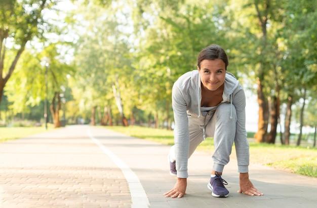 Pełna strzał kobieta przygotowywająca biegać w naturze