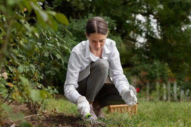 Pełna strzał kobieta trzymająca rękę ogrodniczą grabie