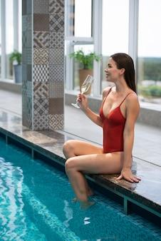 Pełna strzał kobieta trzymająca szklankę