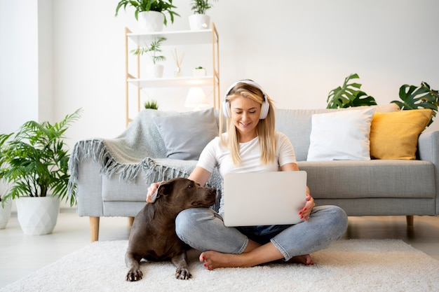 Pełna strzał kobieta z laptopem i psem na podłodze