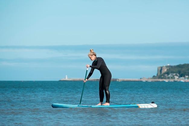 Pełna strzał kobieta z paddleboardingiem w garniturze