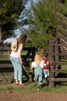 Pełna strzał matka i dzieci na farmie