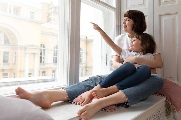Pełna strzał matka i dziewczyna wyglądające przez okno