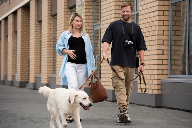 Pełna strzał para spacerująca z uśmiechniętym psem