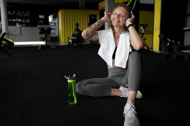 Pełna strzał szczęśliwa kobieta na siłowni